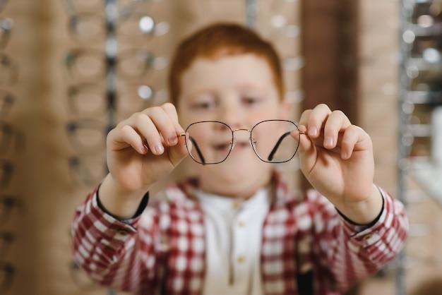 Boy choosing glasses at optics store.