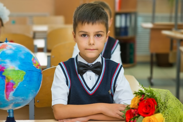 Boy in classroom at desk with globe and bouquet of flowers.