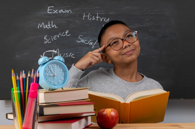A boy in the classroom with chalkboard background.