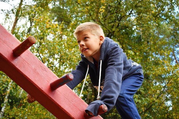 A boy climbing on wooden sports construction