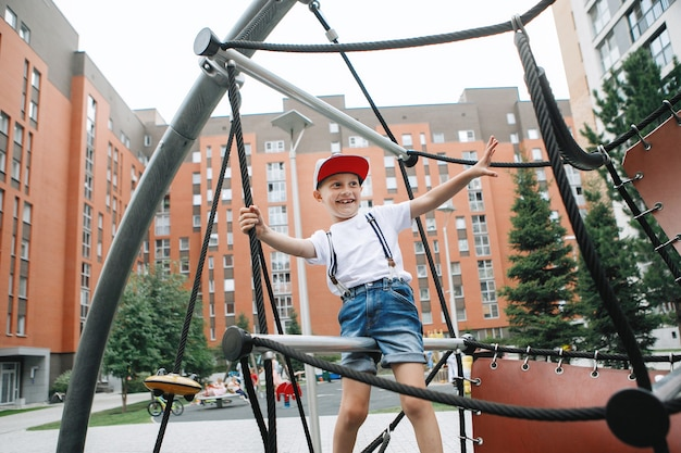 Boy climbs on the rope equipment at the city playground
