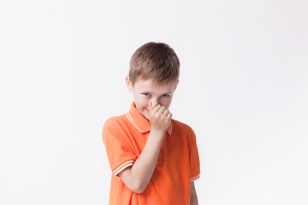 Boy closing his nose with fingers looking at camera on white background