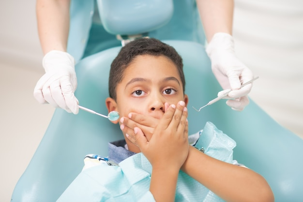 Boy closing mouth. dark-eyed handsome boy closing his mouth while feeling scared of dentist