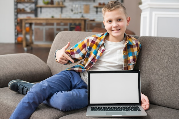 Boy on couch showing laptop screen