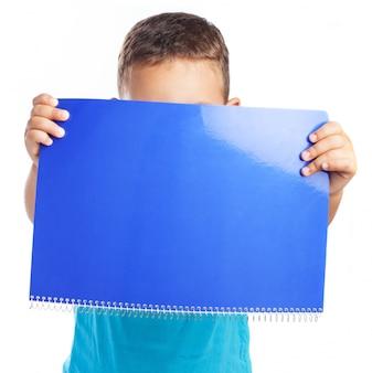 ノートブックで顔を覆っている少年