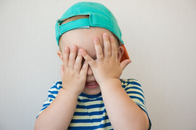 Boy covers his face with hands. portrait. close-up
