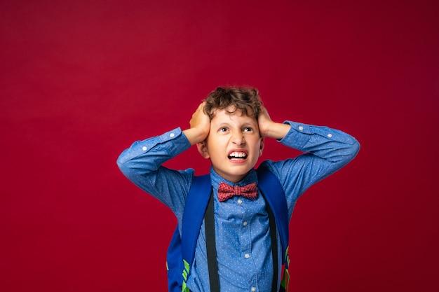 소년은 그의 머리와 귀를 그의 손으로 덮습니다.