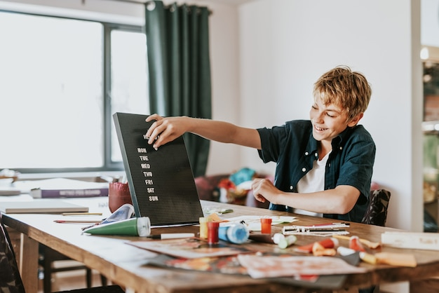 Boy creating text on black letter board