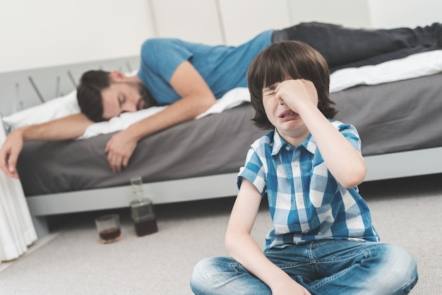 The boy cries while his father sleeps drunk on the bed