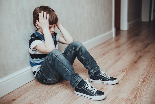 우는 소년은 손으로 얼굴을 가렸습니다. 스트레스를 받는 아이. 가정 폭력과 침략 개념 폭력. 왕따, 우울증 스트레스 또는 좌절에 대한 개념