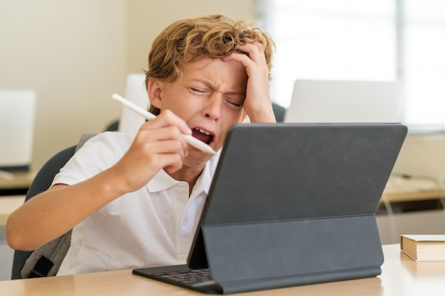 Boy crying and doing hard task on tablet during lesson