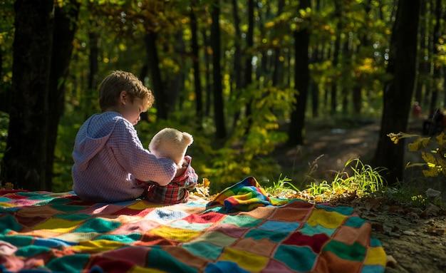 테디 베어 장난감 숲 배경으로 소년 귀여운 아이 놀이. 아이는 좋아하는 장난감을 자연으로 가져갔습니다. 테디베어와 피크닉. 좋아하는 장난감을 가지고 하이킹. 작은 관광객. 행복한 어린 시절. 장난감과 떼려야 뗄 수 없는 관계.