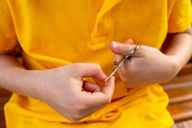 Boy cuts his nails himself