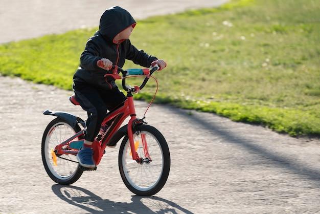 야외에서 자전거를 타는 소년. 아이는 자전거를 타는 법을 배웁니다.