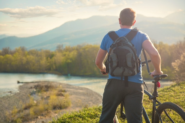 Boy cyclist standing on a mountain and looks at the river at sunset