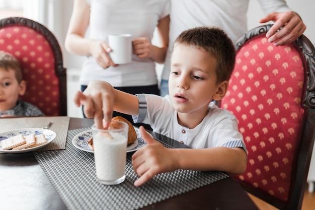Boy dipping biscuit in glass of milk