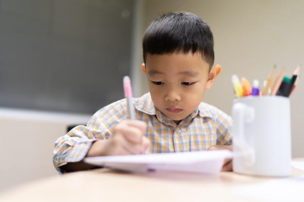 Мальчик делает домашнее задание и сосредотачивается на нем