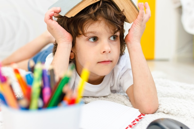 Boy does homework and holds a book on his head in light room. concept reading, education, childhood. social distancing and self isolation in quarantine lockdown.