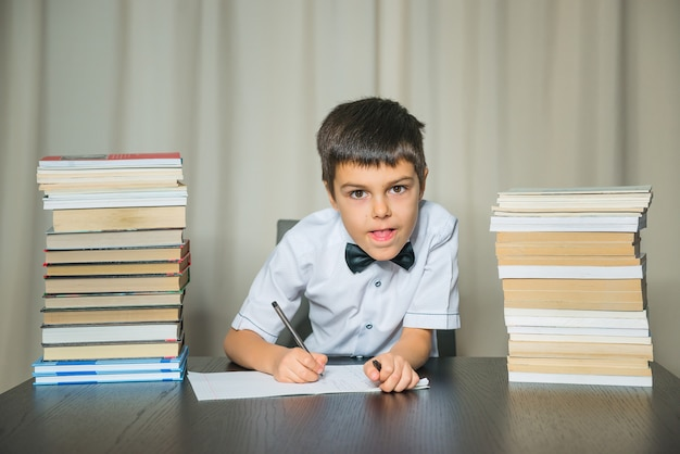 Boy does homework, looking at camera. education, back to school concept.