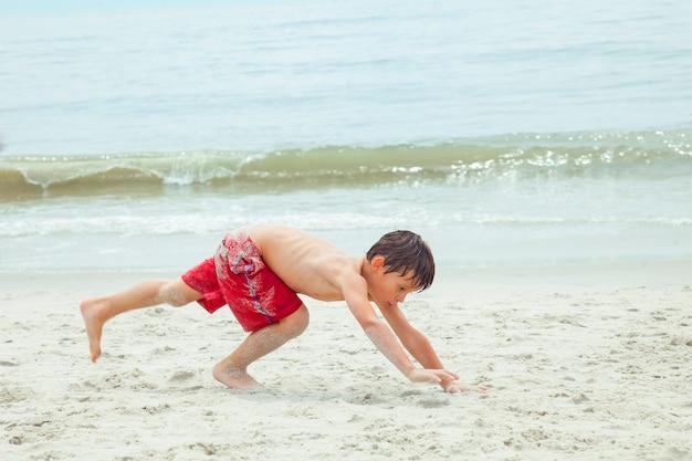ビーチの砂の上で宙返りをしている少年。ビーチで楽しんでいるエキサイティングな子供。海沿いの休暇。子供との野外活動。夏の水泳。