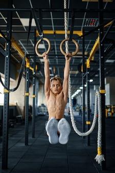 체육관에서 반지에 운동을하는 소년. 스포츠 클럽, 건강 관리 및 건강한 라이프 스타일 훈련, 운동 모범생, 낚시를 좋아하는 청소년