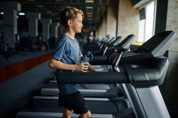 체육관에서 디딜 방 아에 운동을 하 고, 기계를 실행하는 소년. 훈련, 건강 관리 및 건강한 라이프 스타일에 모범생