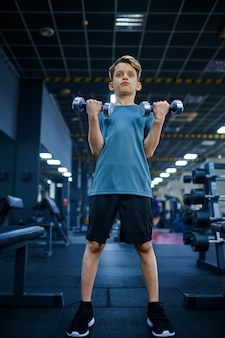 체육관, 하단보기에서에서 아령으로 운동을하는 소년. 스포츠 클럽, 건강 관리 및 건강한 라이프 스타일 훈련, 운동 모범생, 낚시를 좋아하는 청소년