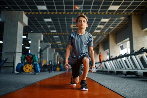 체육관에서 아령으로 운동을하는 소년. 스포츠 클럽, 건강 관리 및 건강한 라이프 스타일 훈련, 운동에 대한 모범생