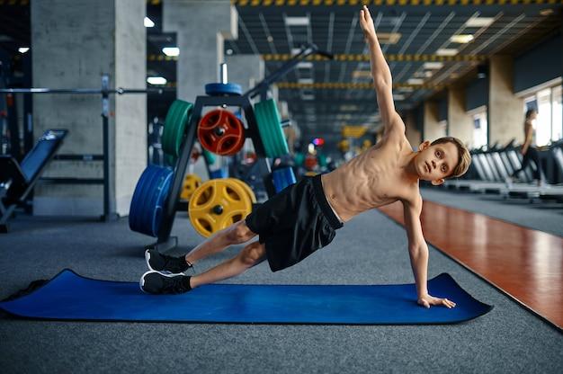 체육관에서 매트에 피트 니스 운동을하는 소년. 스포츠 클럽, 건강 관리 및 건강한 라이프 스타일 훈련, 운동 모범생, 낚시를 좋아하는 청소년