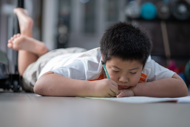 Boy doing homework, child writing paper, education concept, back to school