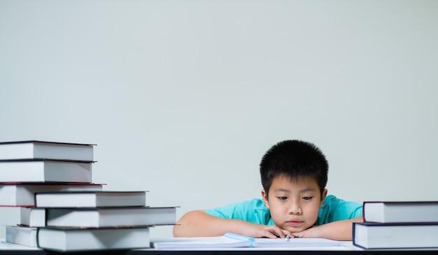 白い壁に宿題をしている少年、教育の概念