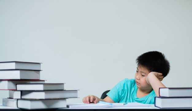 Boy doing homework on white wall, education concept