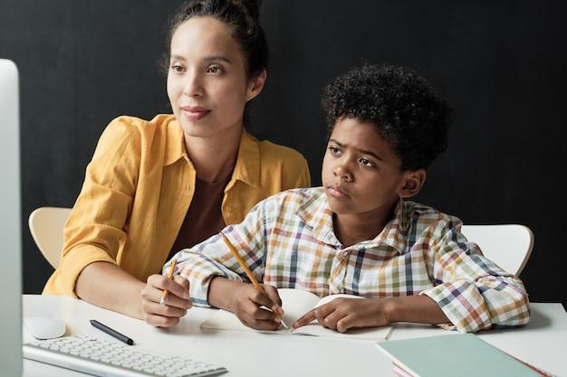 母親と一緒に宿題をしている少年