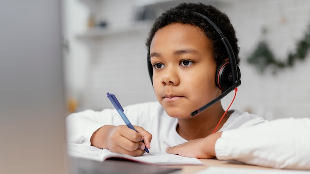 Boy doing homework with use of laptop