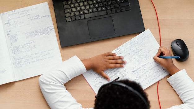 Мальчик делает домашнее задание с помощью ноутбука