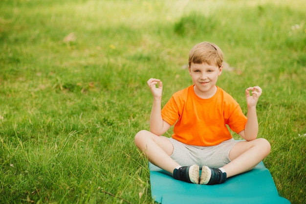 Boy doing yoga outdoors on green grass.