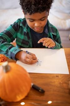 感謝祭のディナーの前に描く少年