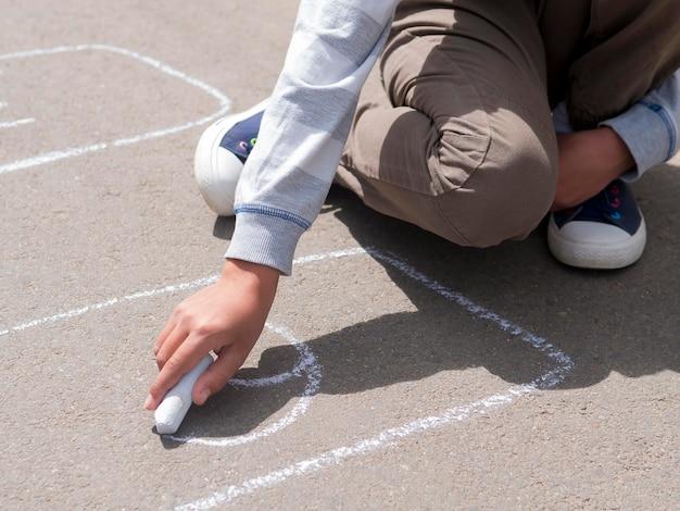 Мальчик рисует на улице мелом