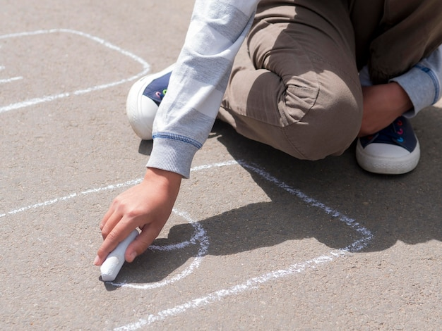 Boy drawing on the street with chalk