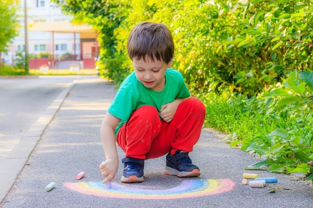 A boy draws a rainbow on the asphalt with crayons