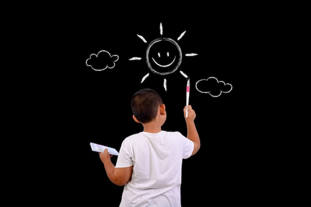 A boy draws the sky and the sun with a chalkboard