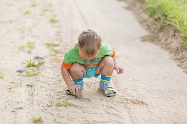 Мальчик рисует камнем на песке, сидя на корточках на песчаной деревенской дороге. мягкий фокус, выборочный фокус