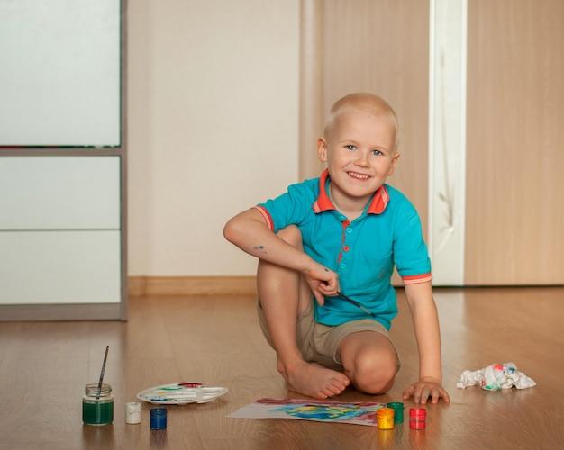 Мальчик рисует красками дома.