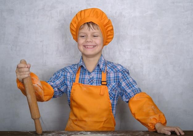 요리사로 옷을 입고 소년은 수제 피자 요리에 종사