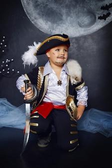 할로윈 장식을 배경으로 해적 옷을 입은 소년