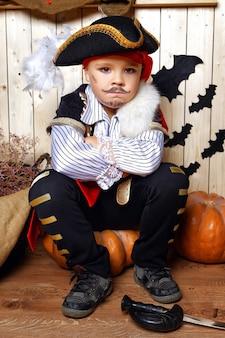 Мальчик одет как пират на фоне декораций хэллоуина