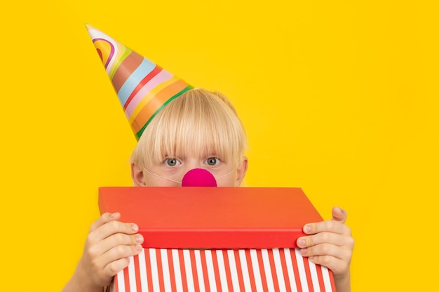 Boy dressed as clown opens the gift box. box with surprise. childrens party.