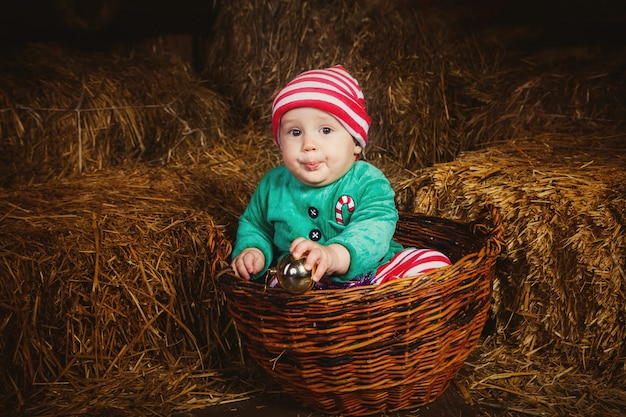 Boy dressed in an elf costume and sits in a basket