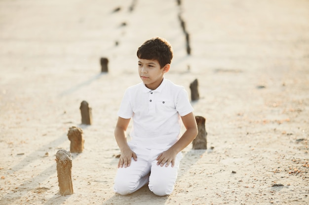 Boy dressed in white clothes is sitting on his knees on the sand on the sunset