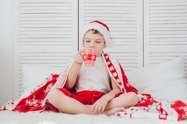 Boy drink cocoa in a mug